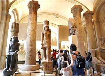 Visitors walk in the Egyptian gallery of the Louvre Museum in Paris.