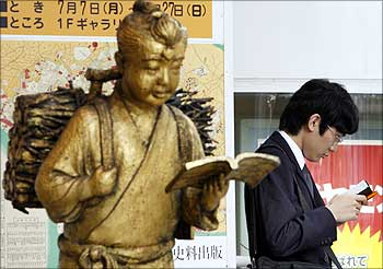 A man reads a book next to a statue in front of a book store in Tokyo.