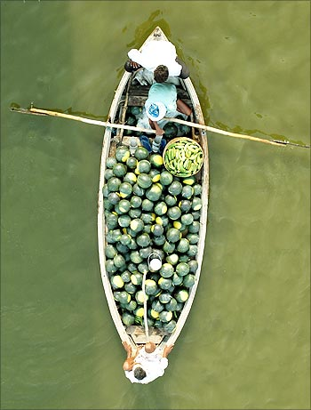 Indian farmers carry watermelons on a boat across the Ganga in Allahabad.
