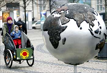 A woman rides a bicycle past a globe in downtown Copenhagen during Copenhagen climate meet in 2009.