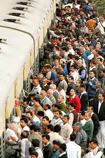 Indian commuters board a crowded train in New Delhi.
