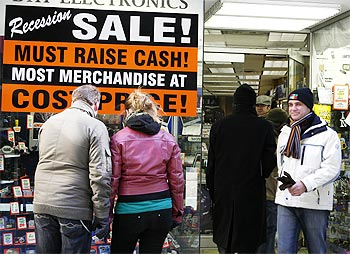 A sign advertises a recession sale outside an electronics store in New York.