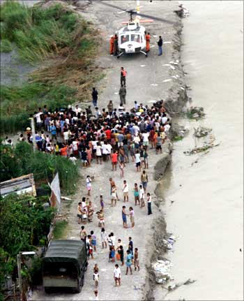 Residents of Minalin town north of Manila waiting as a rescue helicopter delivers relief goods.