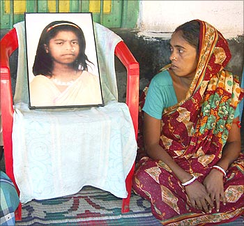 Mother of Tapasi Malik, looks at her photograph.