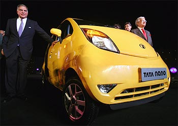 Tata Motors chairman Ratan Tata (left) poses with Nano car.