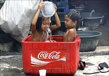 Children take a bath in a soft drink cooler on a hot day in Manila.