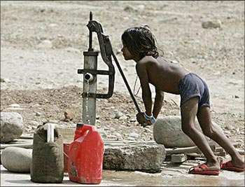 A child works a water pump to draw some water.
