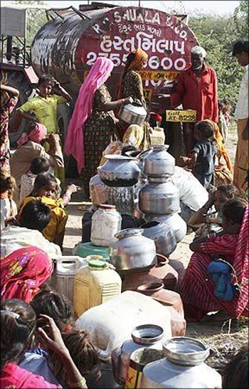 People crowd around a water-tanker in Ahmedabad.
