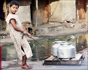 A child pulls a cart with water-filled bowls in it.