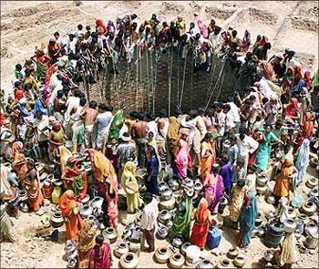 Rural women gather at a well to collect water.