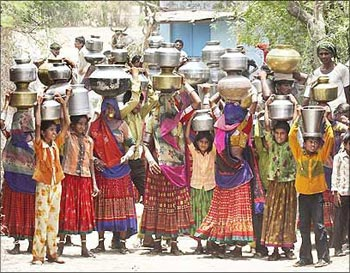 Women carry pitchers filled with drinking water at Siyani village, near Ahmedabad.