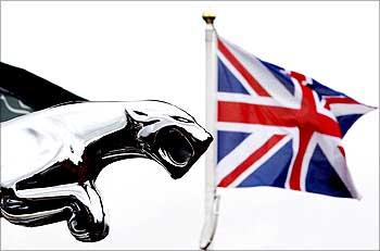 The British flag flies behind a Jaguar car emblem outside a dealership in Manchester.