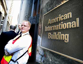 A security guard greets workers outside the AIG headquarters in New York.
