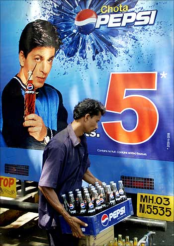 An Indian worker unloads crates of small Pepsi bottles in Mumbai.