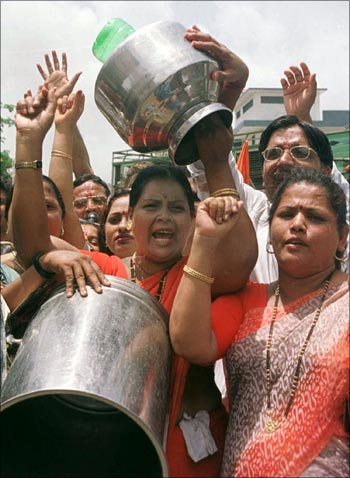 Women carrying empty vessels protest in Mira Road, a Mumbai suburb, over lack of drinking water.