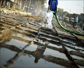 A labourer sprays water on a concrete road at a construction site in Mumbai.