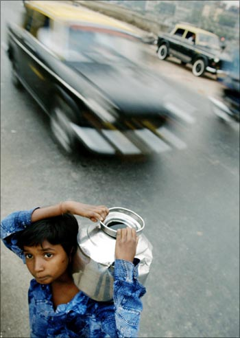 A young boy carries drinking water through a busy road in Mumbai.