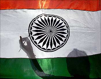 The shadow of a worker is seen as he gives finishing touches to an Indian national flag in Siliguri.