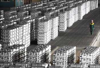 A worker walks past stacks of high purity aluminium ingots at the Khakas aluminium smelter in the Siberian city of Sayanogorsk.