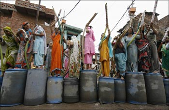 People stand atop their empty containers as they wait for a water tanker from the state-run Delhi Jal (water) Board in New Delhi.