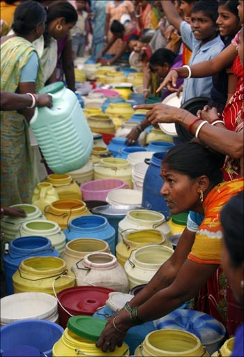 Residents of a slum stand with empty water containers at a roadside in Kolkata.