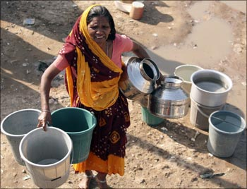 A woman carries empty water containers as she waits to collect drinking water from the municipal corporation tanker.