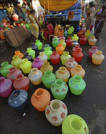 Women wait to fill their containers with drinking water supplied from the municipal corporation tanker.