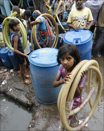 Residents of Sanjay Colony, a residential neighbourhood, carry pipes as they leave after filling their containers from a water tanker provided by the state-run Delhi Jal Board.