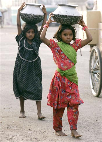 Young girls carry vessels containing drinking water in New Delhi.