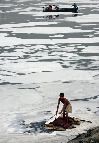 A boy looks for recyclable items in the polluted waters of the Yamuna river.