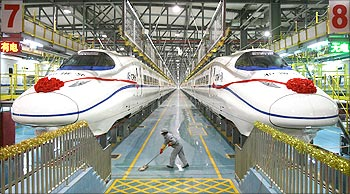 A labourer cleans the floor beside a China Railway High-speed (CRH) train preparing for the operation ceremony from Wuhan to Guangzhou in Wuhan, Hubei province.