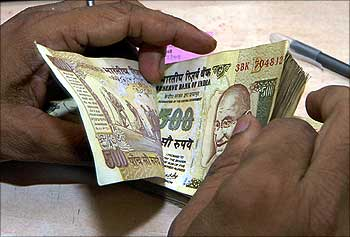 Cashier counts currency notes inside bank in Lucknow