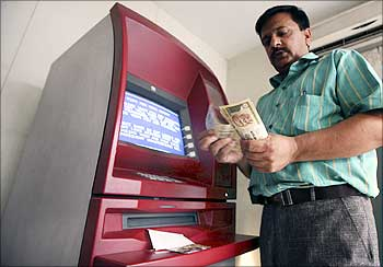 A man counts money after withdrawing it from an ATM in Jammu.