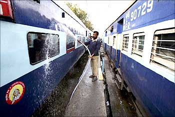 Indian Railway employees wash a passenger train at a railway station.