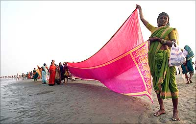 A Hindu woman dries a cloth at the confluence of the Ganges River and the Bay of Bengal at Sagar Island, about 150 km from Kolkata. | Photograph: Jayanta Shaw