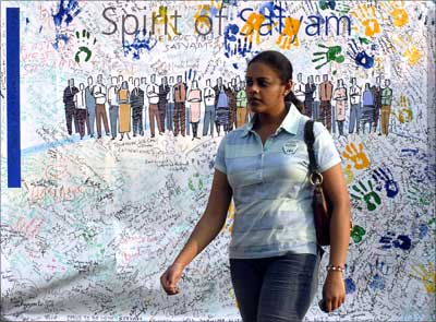 An employee walks past a banner with signatures of employees expressing the spirit and unity at the Satyam Computer Services head office in Hyderabad.