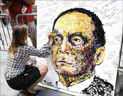 A Lehman Brothers Holdings Inc employee writes a message on a portrait of Dick Fuld in New York