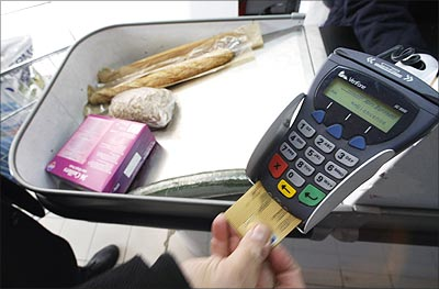 A shopper pays with his credit card in a supermarket in Nice in France.   Photograph: Eric Gaillard/Reuters