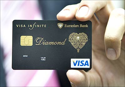 Dmitry Nikolin, executive director of Eurasian Bank, shows a new VISA card encrusted with a 0.02 carat diamond and laced with an elaborate gold pattern in Almaty. | Photograph: Shamil Zhumatov/Reuters