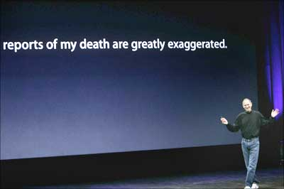 Steve Jobs takes the stage beneath a sign that makes light of reports on his health.