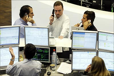 Traders talk on their phones at the Frankfurt Stock Exchange.