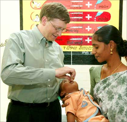 Bill Gates gives an oral polio drop to a baby at a health clinic in Andhra Pradesh.