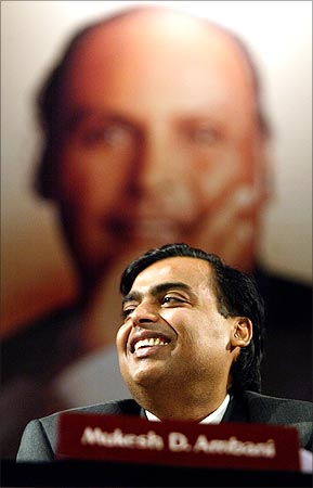Reliance Industries chairman Mukesh Ambani, with the image of his father Dhirubhai Ambani in the backdrop.