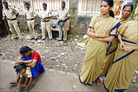 A woman and a child sit near Indian policemen during a protest against SEZ in Mumbai.