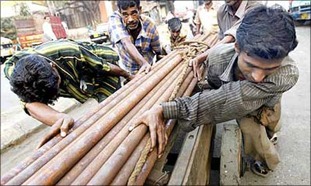 Indian workers pull a cart laden with steel pipes in Mumbai.