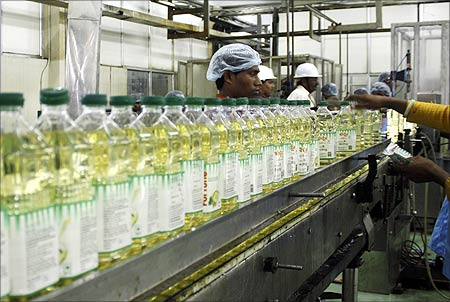Employees fill plastic bottles with edible oil at an oil refinery plant in Mundra near Ahmedabad.