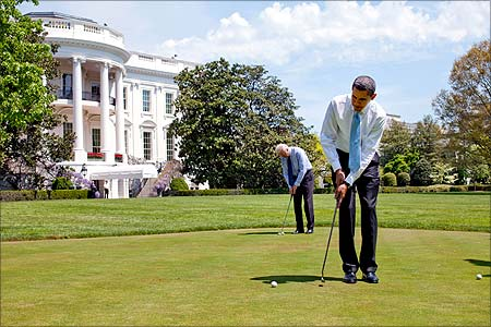 US President Barack Obama and Vice President Joe Biden practice their putting on the White House putting green.