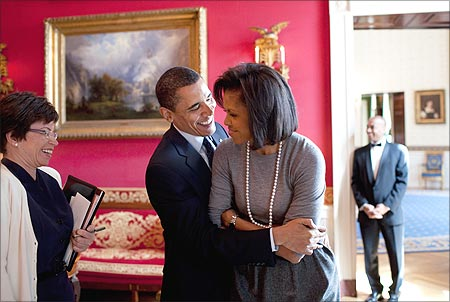 Obama hugs his wife, Michelle, in the White House Red Room as Senior Advisor Valerie Jarrett smiles.