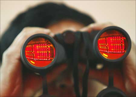 A man uses binoculars as he monitors stock movements at a stock exchange.
