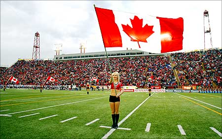 A Calgary Stampeders cheerleader flies a Canadian flag during Canada Day.